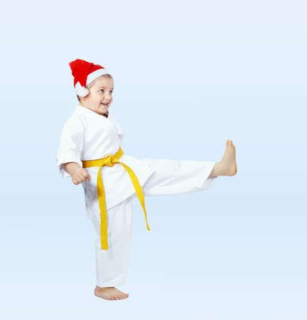 Karateka in the cap of Santa Claus hits a kick leg