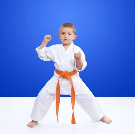 Boy in karategi worth in rack karate Stock Photo