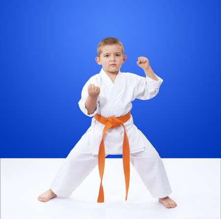 In rack is karate is standing athlete with an orange belt
