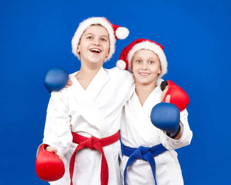 Children in Santa Claus caps and of red and blue overlays on hands Stock Photo