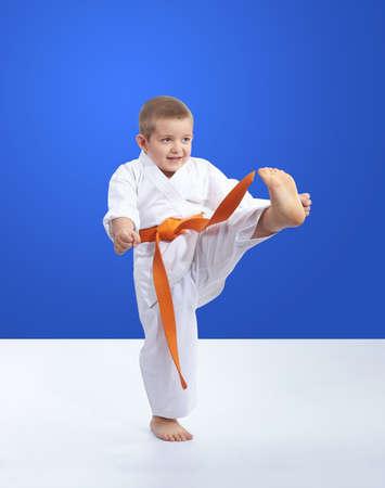 On a blue background karateka is training kick leg forward