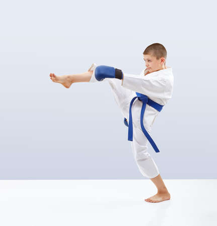 Boy with blue belt and overlays on the hands is beating kicking Stock Photo