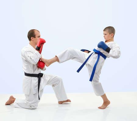 Sportsman with a blue belt is training kick leg on the simulator