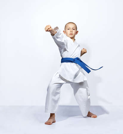 Straight punch arm karateka is beating with a blue belt Stock Photo