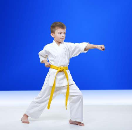 On light blue background athlete beats punch arm