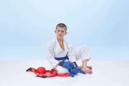 Sportsman in karategi sits near a karate outfit