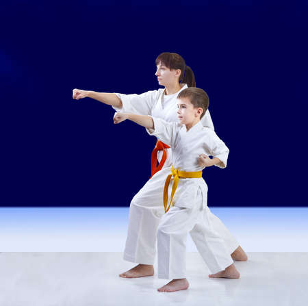 On a dark blue background the athletes mom and son are training punch arm