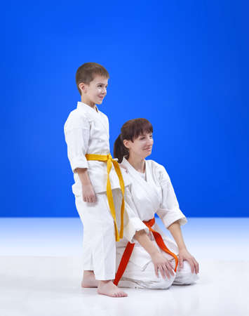 On a blue background mother and son the athletes with a smile on his face Stock Photo