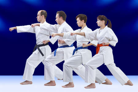 Sportsmen with different colors of belts are training punch arm Stock Photo