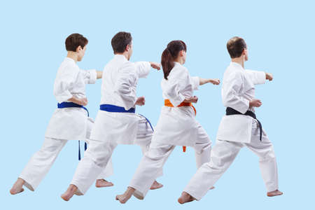 Four sportsmen are hitting with a hand on a light blue background Stock Photo