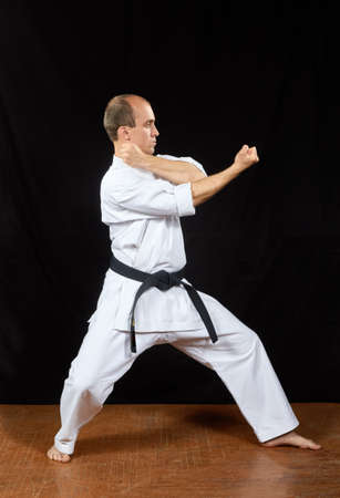 On a black background, the master trains karate blocks Stock Photo