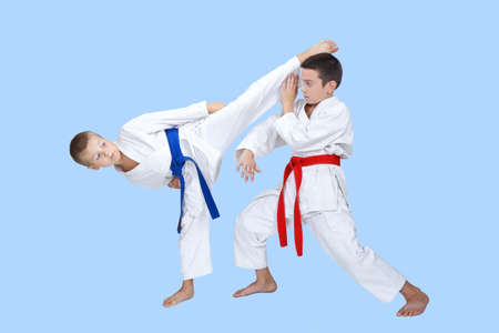 Two boys train a circular kick and block Stock Photo