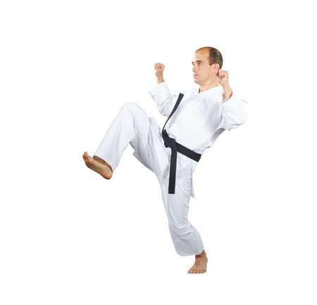 Blocks hands and kick leg is doing an athlete in karategi