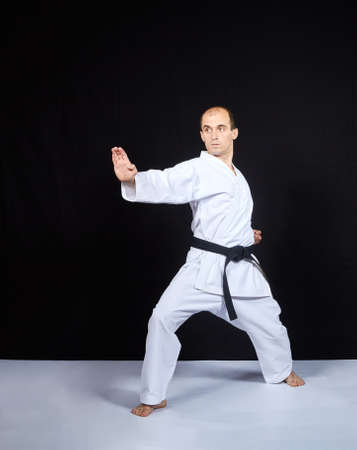 On a black background, an athlete in karategi trains a block with his hand Standard-Bild