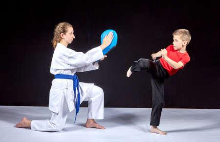 그 소년은 시뮬레이터에서 운동 선수의 손에 킥을 때린다.