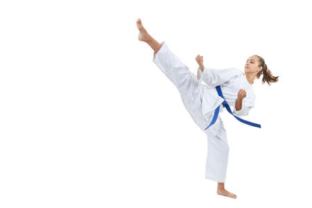 A high circular kick is struck by an athlete with a blue belt Stock Photo