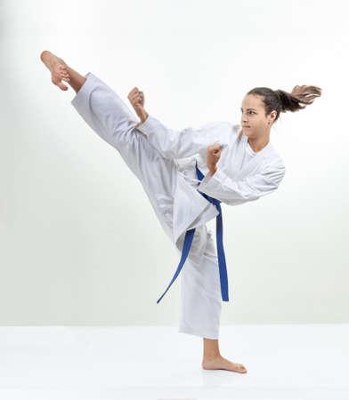 Girl athlete is training kick leg