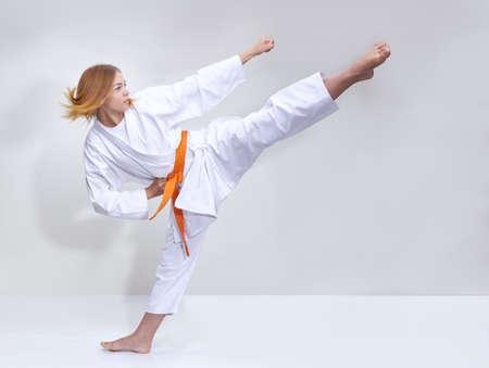 Con una cintura arancione la ragazza batte un calcio Archivio Fotografico - 84467553
