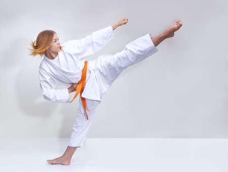 With an orange belt the girl beats a kick