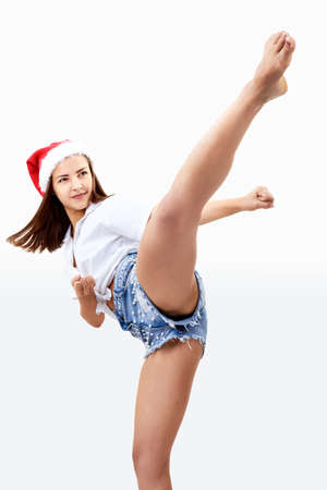 Beautiful girl in a Santa Claus hat is beating kick Imagens