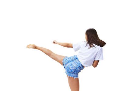 Sportvrouw in korte broek verslaat kick geïsoleerd Stockfoto