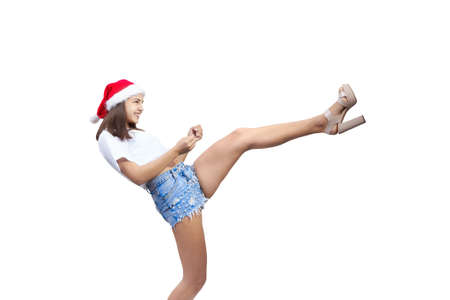 A beautiful girl in a Santa Claus hat is beating kick isolated