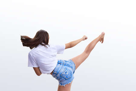 On a light background a girl in shorts beats a kick Stock Photo