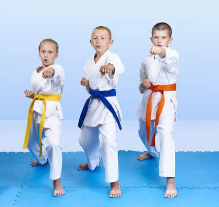 On a blue mats three athletes beat punch arm