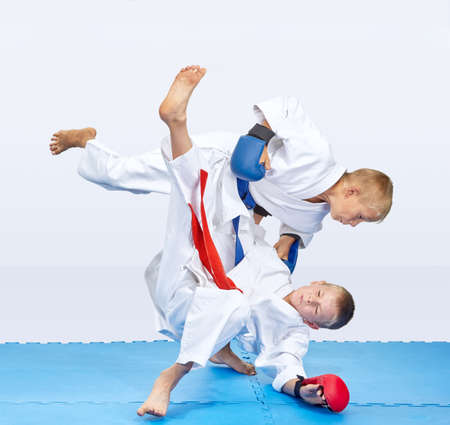With blue and red overlays on hands boys are training judo throws