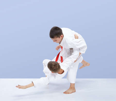Boys in judogi are training throws