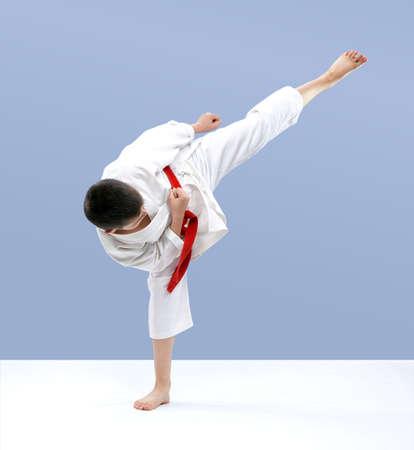 Karate athlete hits a kick on a light background Zdjęcie Seryjne