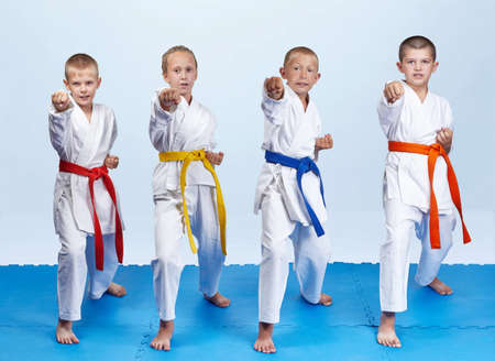 Four karateka in karategi are beating punch arm