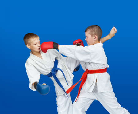 Punches and kicks boys are beating in karategi Stock Photo