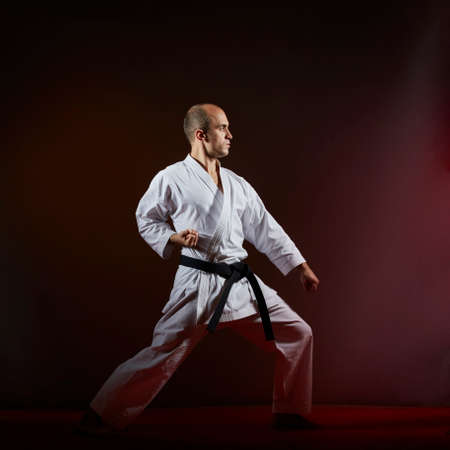 On a dark background, an athlete in karategi makes formal karate exercises