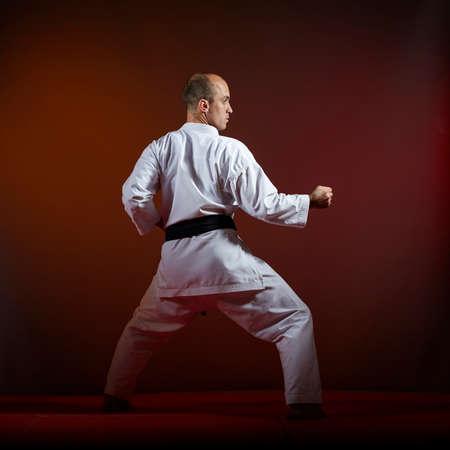 On a dark background, an athlete with a black belt does formal karate exercises Reklamní fotografie