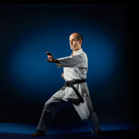 Adult athlete performs formal karate exercises on a blue tatami Stock Photo