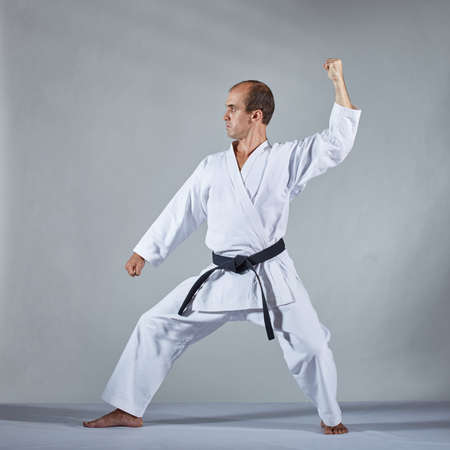 In karategi athlete doing formal karate exercises on a gray background