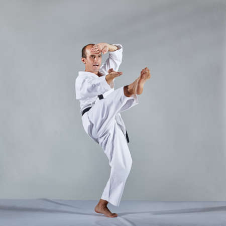 In karategi, an athlete performs formal karate exercises on a gray background