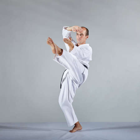 On a gray background athlete in karategi athlete trains formal karate exercises