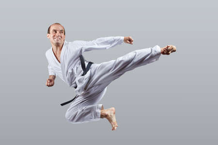 Adult man performs a kick to the side in a jump on a gray background Banco de Imagens