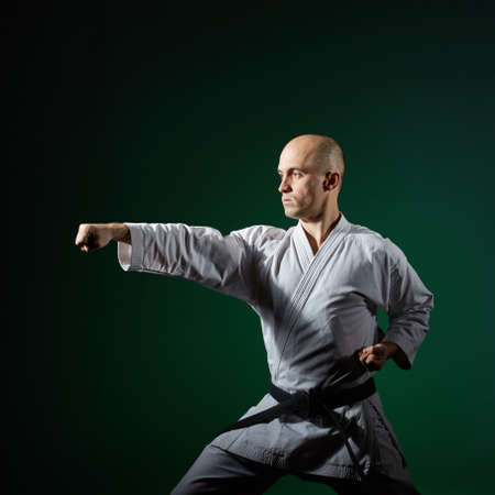 Against dark green background the athlete trains formal karate exercises