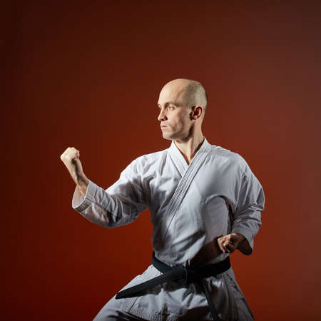 Athlete trains formal karate exercises against a burgundy background
