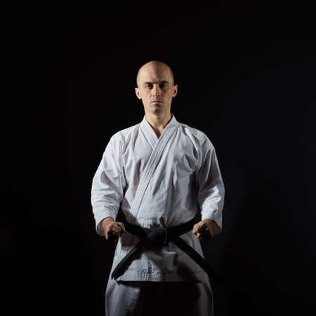 On a black background athlete with a black belt is in the stance of karate