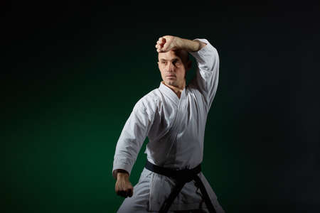 Adult athlete trains formal karate exercises on a dark green background