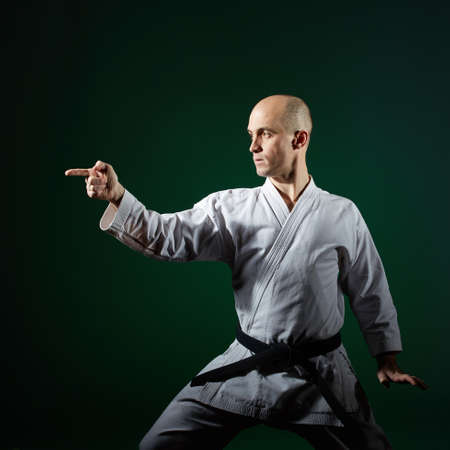 Against the dark green color, the athlete does formal karate exercises