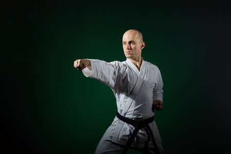 Athlete doing formal karate exercises on a dark green background