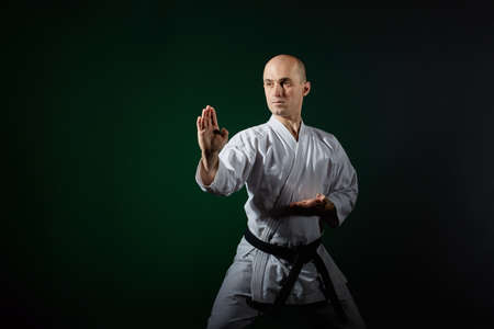 Athlete performs formal karate exercises on a dark green background
