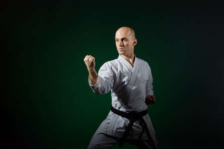 Athlete trains formal karate exercises on a dark green background