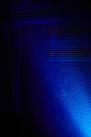 Light blue diagonal beam of light on a blue background with patterns Reklamní fotografie