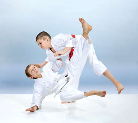 Boys doing judo throws on a light background